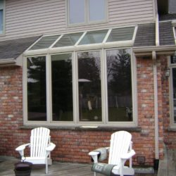 Built in sunroom-style windows installed into brick wall.