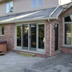 Rear of house showing sliding patio doors, wooden deck and covered jacuzzi.