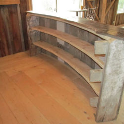 Back of curved wooden bar with built in shelving.