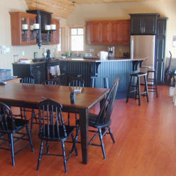 country style open concept kitchen. Dark wood island, hard wood floors and a traditional wooden dining table with 8 chairs