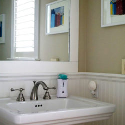 large mirror above pedestal sink surrounded by tan walls with white wainscoting
