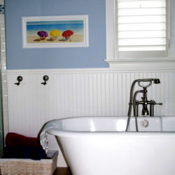 bathroom with traditional looking bathtub, blue walls with white wainscoting