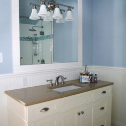 bathroom with large mirror, white vanity with brown counter, blue walls with white wainscoting