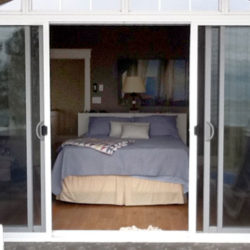 bedroom viewed through open French-style sliding glass doors
