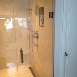 close up of large square glass shower enclosure, ceiling mounted shower head, knobs and hand-held shower head