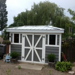 Grey and white shed with metal roof.
