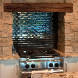 dark ceramic back splash for gas stove, surrounded by stone enclosure with large wooden beam lintel