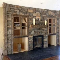 Field stone fireplace with built in wood storage and cabinets.