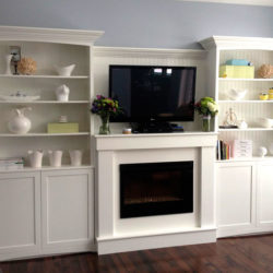 Classic white shelving unit with built in entertainment unit above the fireplace.