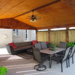 Outdoor entertainment area covered by wooden slat cathedral ceiling. Outdoor table, chairs and couch.