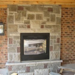 Stone fireplace against a brick wall.