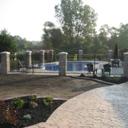 Concrete stone-style walkway leading to pool. Pool surrounded by fence made of black painted steel and stone pillars.