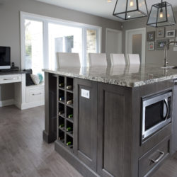 large wooden kitchen island, dark wood with marble top. Contains cupboards, microwave, sink, built-in wine rack and dish washer. Four chair backs visible over island.