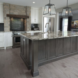 open concept kitchen with white cabinets, large dark wood and marble island, stone enclosure for gas stove with wooden beam lintel, hard wood floors