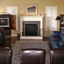 living room with classic white fireplace, area rug over hardwood floors, tv cabinet and leather furniture