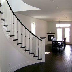 Dining area adjacent to large curving staircase.
