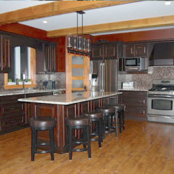 open concept kitchen, long island that seats 5, dark wooden cabinets, hard wood floors and exposed wood beams in ceiling