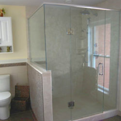 bathroom with square glass shower, small white wall vanity and toilet