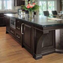large, solid kitchen island, dark wood with granite top. Built in microwave.