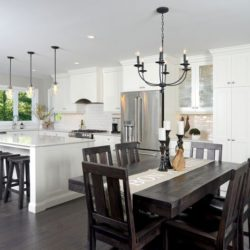 Open concept kitchen and dining room. Kitchen is primarily white. Dining room contains solid dark wood table and 6 chairs. Dark hardwood flooring throughout.
