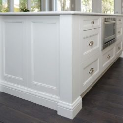 White kitchen island, photographed from below the top of the counter. Dark wooden floors.