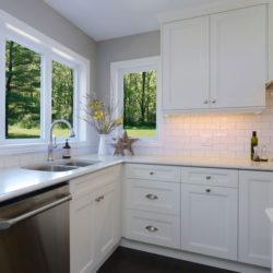 Kitchen corner cabinets, white flat panel cabinet doors. Double sink below large windows, dishwasher in the foreground.