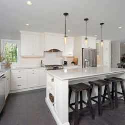 Kitchen cabinets and pantry, white flat panel doors/drawers. Stainless steel double door refrigerator and gas stove. White kitchen island with three dark wooden stools.