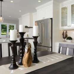 Dining room off of the kitchen. Dark wood table with large, dark wooden candle holders, white candles. White cabinets with crown molding.