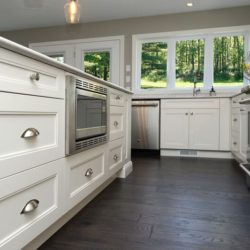 On the left, white kitchen island, photographed from below the top of the counter. Dark wooden floors. On the right - cabinets, stove.
